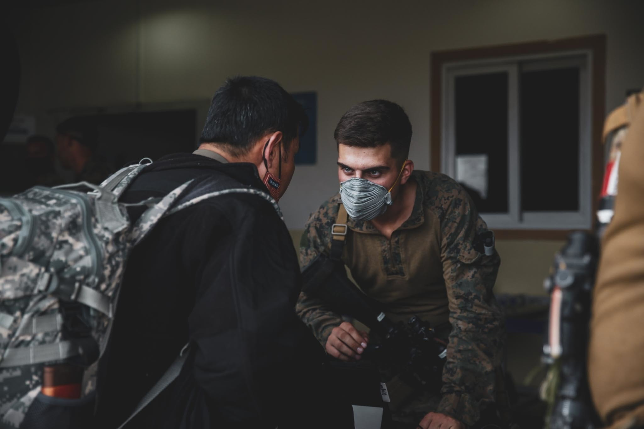 A Marine assigned to the 24th Marine Expeditionary Unit (MEU) processes an evacuee at Hamid Karzai International Airport, Kabul, Afghanistan, August 15. U.S. Soldiers and Marines are assisting the Department of State with an orderly drawdown of designated personnel in Afghanistan. (U.S. Marine Corps photo by Sgt. Isaiah Campbell)