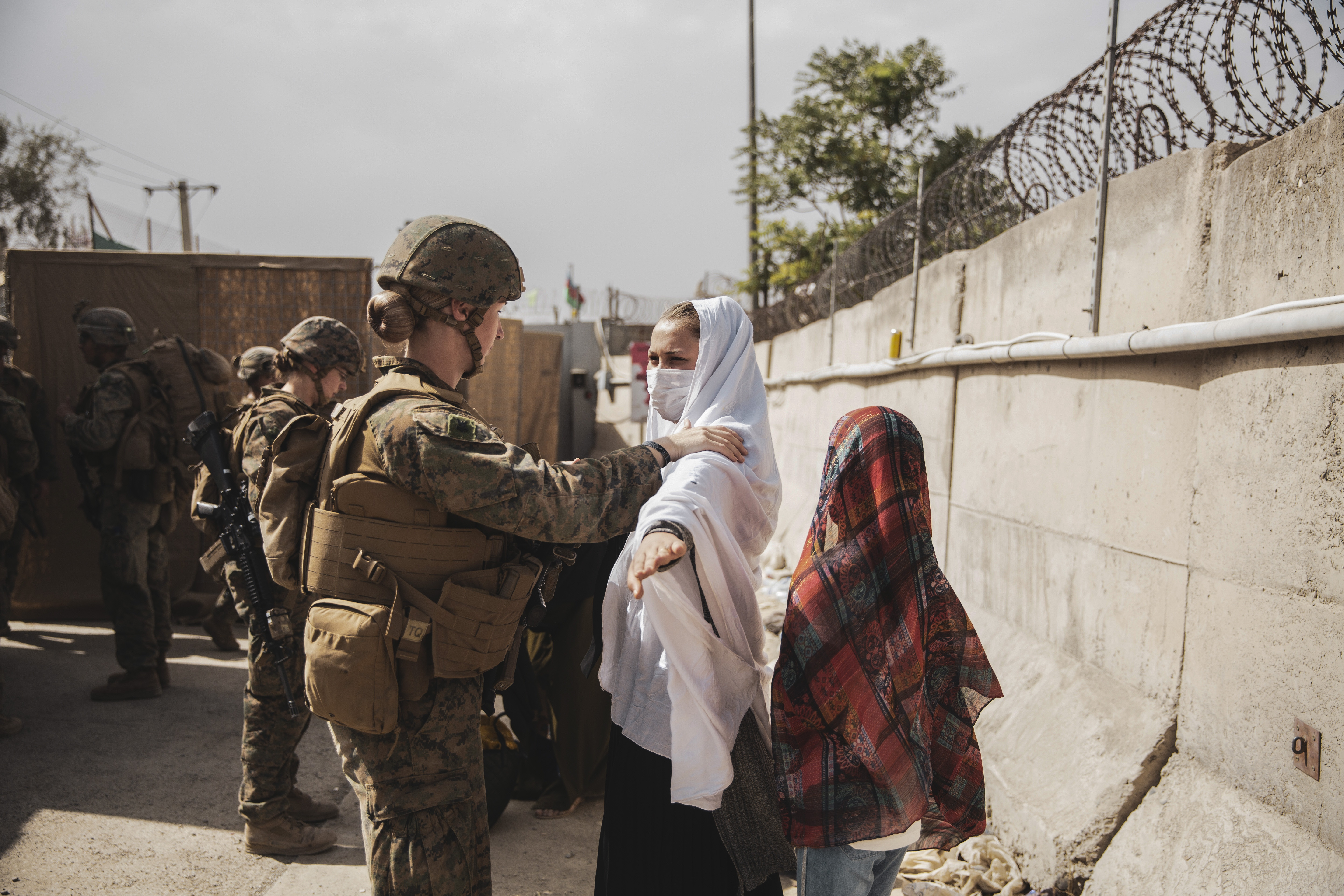 A Marine checks two civilians during processing through an Evacuee Control Checkpoint (ECC) during an evacuation at Hamid Karzai International Airport, Kabul, Afghanistan, Aug. 18. U.S. Marines are assisting the Department of State with an orderly drawdown of designated personnel in Afghanistan. (U.S. Marine Corps photo by Staff Sgt. Victor Mancilla)