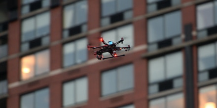A quad-copter camera drone flies over crowds gathered to attend the