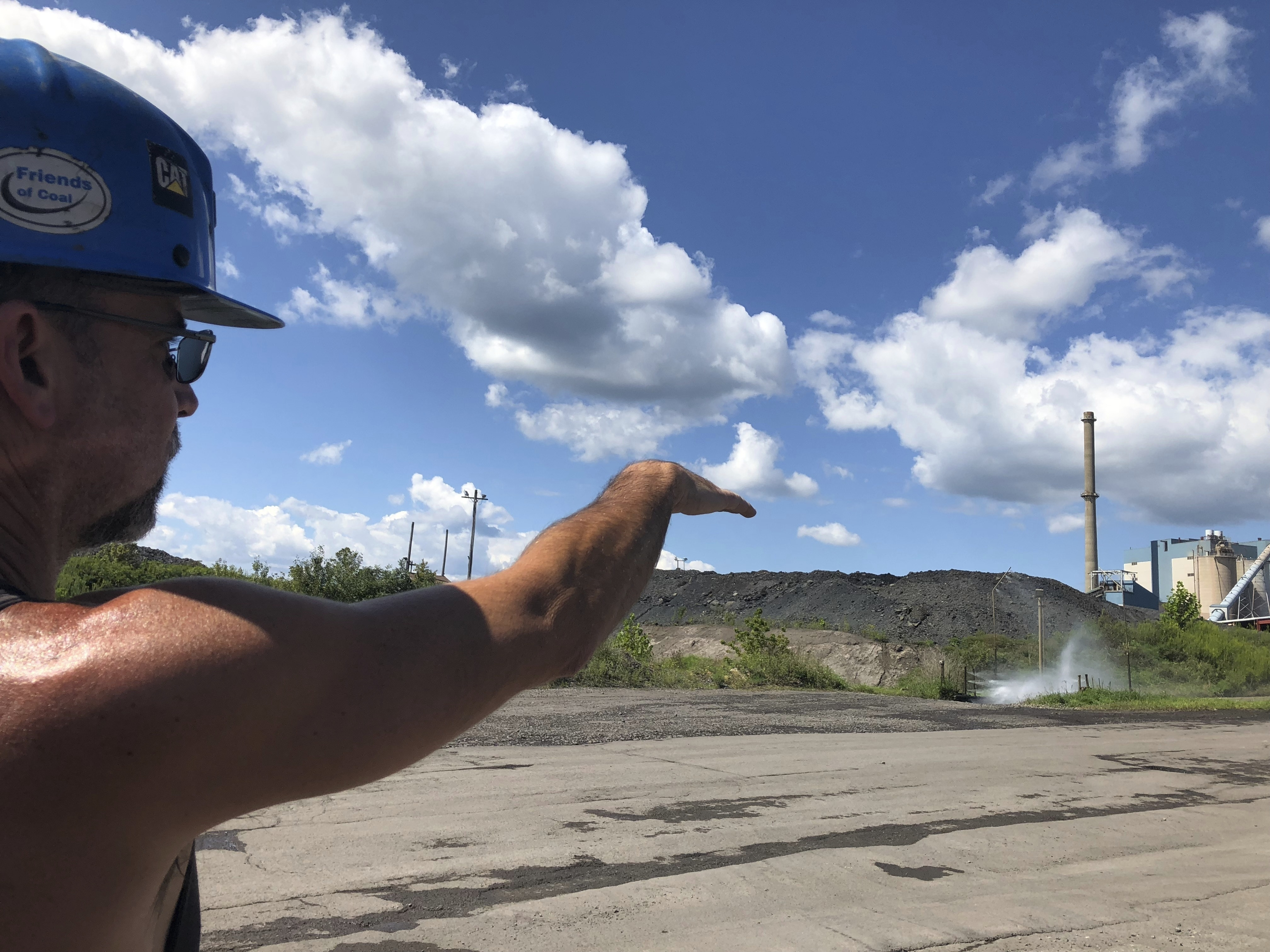 Brian Weekly, a contractor at West Virginia's Grant Town coal-fired power plant, gestures toward the small facility's smokestack, Thursday, Aug. 23, 2018 in Grant Town, W.Va. Weekly says opponents of the coal industry are behind warnings of health risks from smokestack emissions under the Trump administration's plan. President Donald Trump picked West Virginia where he announced rolling back pollution rules for coal-fired power plants. But he didn't mention that the northern two-thirds of West Virginia, with the neighboring part of Pennsylvania, would be hit hardest.  (AP Photo/ Ellen Knickmeyer)