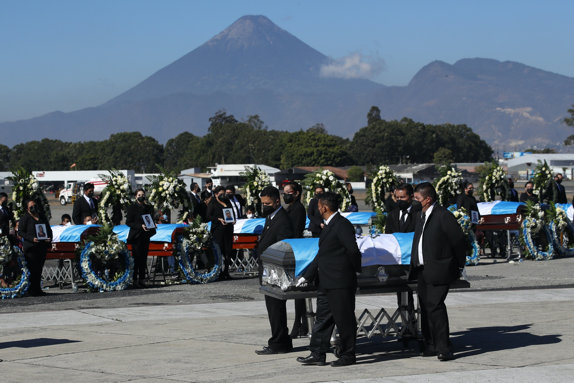 Flag draped coffins carrying the remains of Guatemalan migrants who were killed near the U.S.-Mexico border in January arrive to the Air Force base in Guatemala City, Friday, March 12, 2021. The migrants were among 19 people shot and burned in Camargo, located in the northern Mexican state of Tamaulipas on Jan. 22. (AP Photo/Moises Castillo)