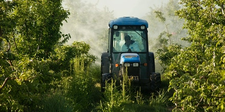BANKWE Farmer operating tractor with attached spray rig applying pesticide.