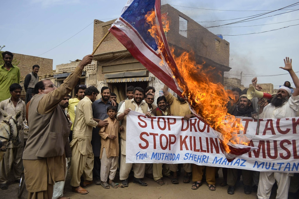 Activists of Pakistan Muthidda Shehri Mahaz burn the US flag during a protest in Multan on March 14, 2012, against US drone attacks. A US drone strike in Pakistan's lawless tribal belt on March 13 killed eight fighters supporting the Taliban in Afghanistan but not hostile to Pakistani authorities, local officials said. AFP PHOTO/S S MIRZA (Photo by Shahid Saeed MIRZA / AFP) (Photo by SHAHID SAEED MIRZA/AFP via Getty Images)