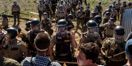 """Law enforcement officers stand off against demonstrators at an Enbridge Line 3 pump station during a """"Treaty People Gathering"""" protest in Hubbard County, Minn., on June 7, 2021."""