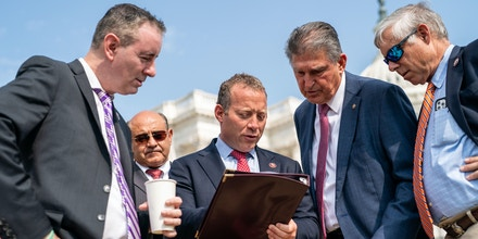 WASHINGTON, DC - JULY 30: Rep. Brian Fitzpatrick (R-PA), Rep. Josh Gottheimer (D-NJ), Sen. Joe Manchin (D-WV), and Rep. Fred Upton (R-MI) talk before the Problem Solvers Caucus news conference on the Infrastructure Deal at the House Triangle in front of the U.S. Capitol Building on Friday, July 30, 2021 in Washington, DC. (Kent Nishimura / Los Angeles Times via Getty Images)