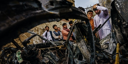 Relatives and neighbors of the Ahmadi family gather around the incinerated husk of a vehicle targeted and hit by an American drone strike, which killed 10 people including children, in Kabul on Aug. 30, 2021.