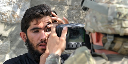 A US army soldier scans the eyes of an Afghan resident with an Automated Biometric Identification System during a mission at Turkham on October 6, 2011.