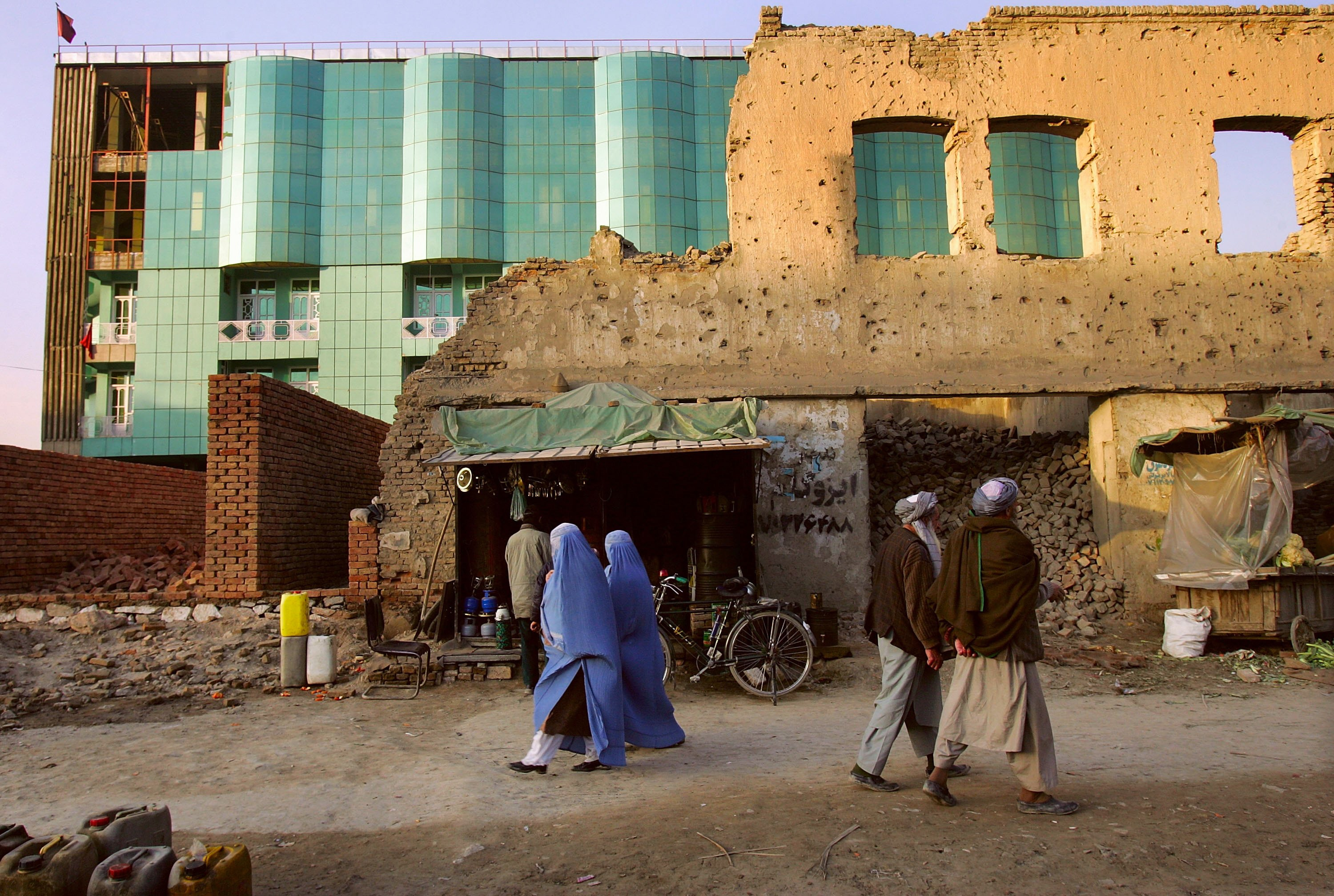 KABUL, AFGHANISTAN - FEBRUARY 08: Afghans walk near a new hotel built amidst Afghan civil war ruins on February 8, 2006 in Kabul, Afghanistan. Construction is booming across Afghanistan, fueled by an influx of foreign aid and investments from returning Afghan expatriates. Many say drug money from the nation's heroin cultivation is often laundered through constuction projects as well. (Photo by John Moore/Getty Images)