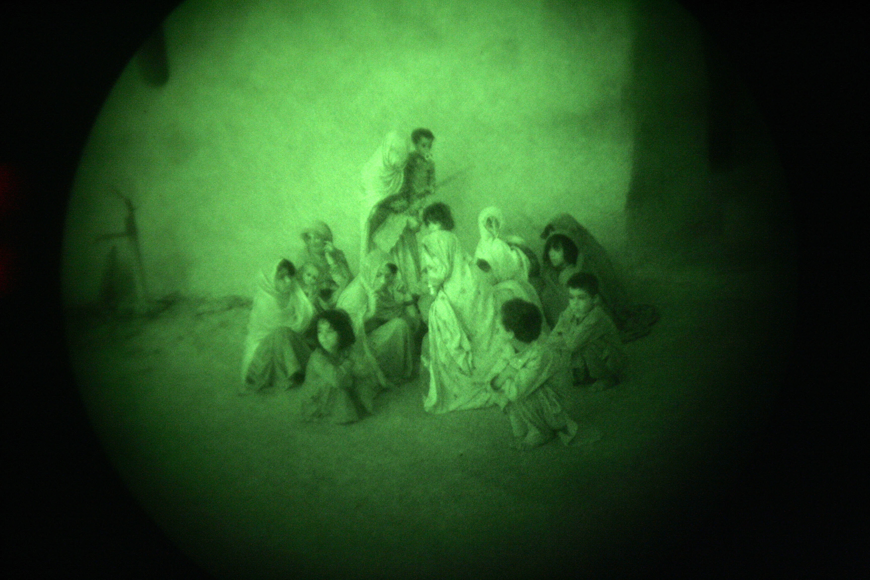 Afghan women and children gather in a co
