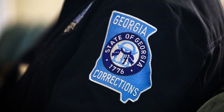 A clothing patch showing the insignia of the Georgia Department of Corrections is worn by an officer.