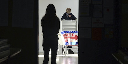 First-time voter Baylee Fidler, 19, waits in the doorway for a voting booth as Tom Davis, background, completes his ballot at the Boot City Opry near Terre Haute, Ind., on Tuesday, Nov. 3, 2020.