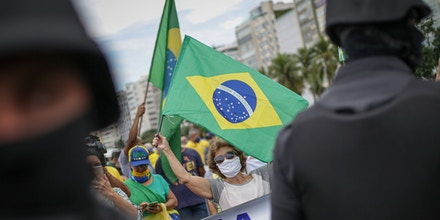 A woman waves a Brazilian flag while police officers stand during a rally in support of Brazil's President Jair Bolsonaro on June 7, 2020 in Rio de Janeiro, Brazil.