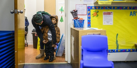 Baltimore, Maryland United States - January 12: Teacher Keshawna Edwards zips up the coat of Montana Mason, 3, before recess at Little Flowers Early Childhood and Development Center in the Sandtown-Winchester neighborhood of Baltimore, Maryland on January 12, 2021. Crystal Hardy-Flowers, owner and founder of Little Flowers Early Childhood and Development Center, died from COVID-19 complications December 31st. She was 55. Her daycare, located in the Sandtown-Winchester neighborhood of West Baltimore, re-opened from winter break Monday January 11th, with her absence felt by staff and the older students.(Photo by Matt Roth for The Washington Post via Getty Images)