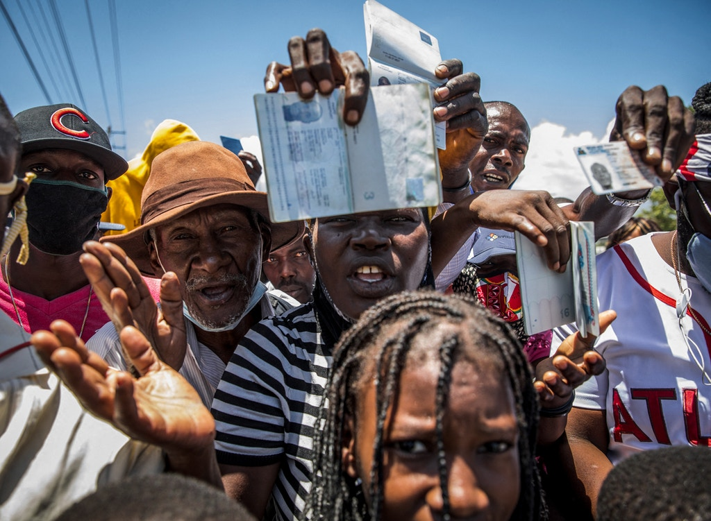 """Haitian citizens hold up their passports as they gather in front of the US Embassy in Tabarre, Haiti on July 10, 2021, asking for asylum after the assassination of President Jovenel Moise explaining that there is too much insecurity in the country and that they fear for their lives. - The widow of slain Haitian leader Jovenel Moise, who was critically wounded in the attack that claimed his life, issued her first public remarks since the assault, calling on the nation not to """"lose its way."""" According to Haitian authorities, an armed commando of 28 men -- 26 Colombians and two Haitian-Americans -- burst in and opened fire on the couple in their home. So far, 17 have been arrested, and at least three were killed. A handful remain at large, police say. No motive has been made public. (Photo by Valerie Baeriswyl / AFP) (Photo by VALERIE BAERISWYL/AFP via Getty Images)"""
