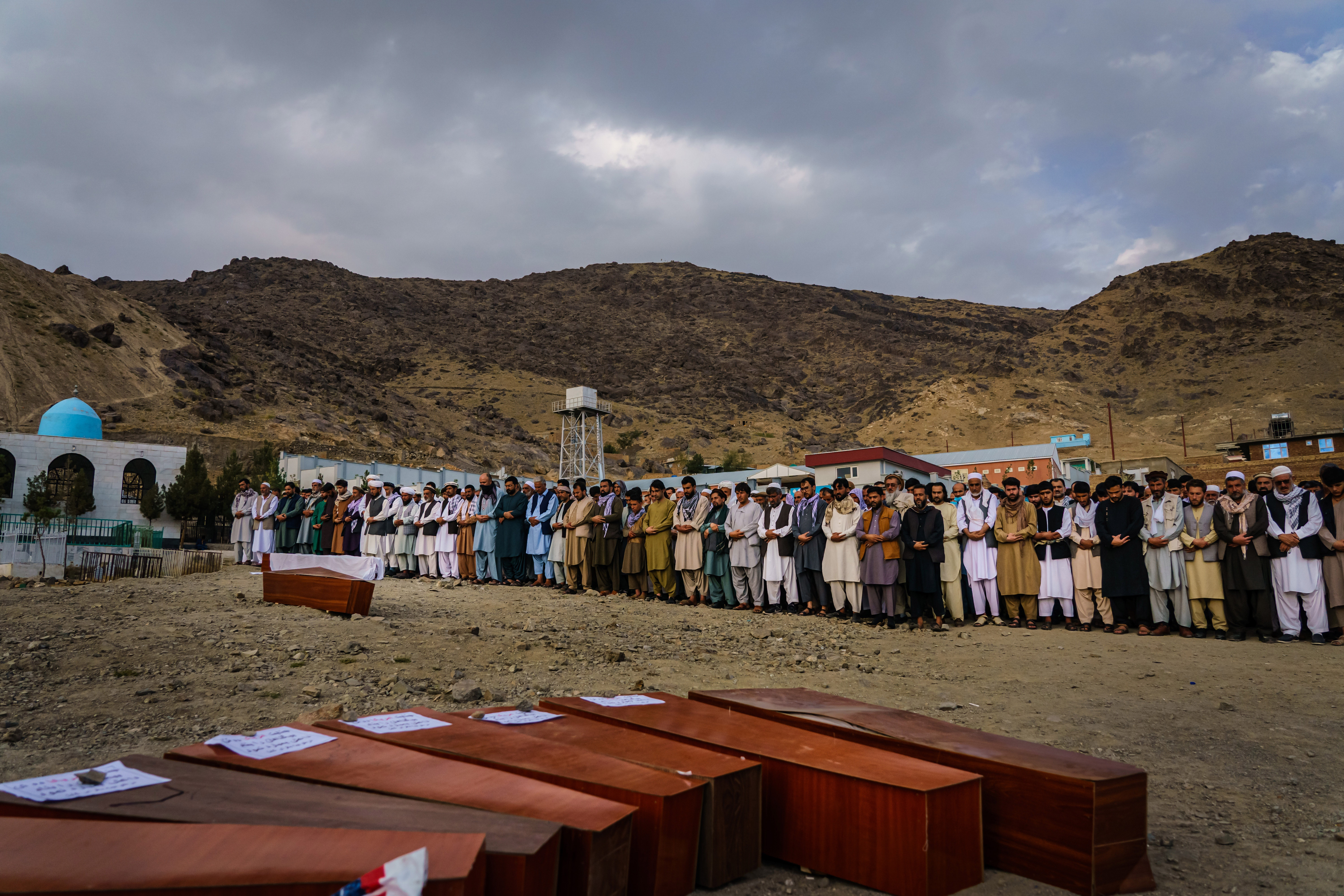 KABUL, AFGHANISTAN -- AUGUST 30, 2021: Islamic prayers are recited for the bodies before they could be laid into the ground to be buried, as around 200 people attend a mass funeral for the 10 members of a family that is said to have been killed by a U.S. drone strike, in Kabul, Afghanistan, Monday, Aug. 30, 2021. (MARCUS YAM / LOS ANGELES TIMES)