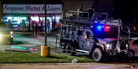 A St. Louis County  police officers respond in an MRAD vehicle after shots were fired during a protest march on August 9, 2015 on West Florissant Avenue in Ferguson, Missouri. Over 50 shots were reportedly exchanged on the day marking the one year anniversary of the death of an unarmed black teen, Michael Brown, who was shot and killed by a white police officer, throwing America's troubled race relations into harsh relief.     AFP PHOTO / MICHAEL B. THOMAS        (Photo credit should read Michael B. Thomas/AFP via Getty Images)