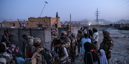 Afghans hoping to gain entry to the Hamid Karzai International Airport are contained by fighters from the notorious CIA-backed paramilitary unit known as 01, in Kabul on Aug. 24, 2021.