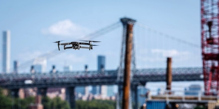 A SZ DJI Technology Co. Mavic 2 Zoom drone flies over the Brooklyn Navy Yard during an event in the Brooklyn Borough of New York, U.S., on Thursday, Aug. 23, 2018. DJI introduced two additions to the Mavic series: the Mavic 2 Pro, with an integrated Hasselblad camera, and the Mavic 2 Zoom, a foldable consumer drone with optical zoom capability. Photographer: Mark Kauzlarich/Bloomberg via Getty Images