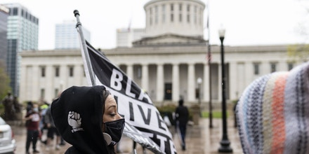 Activist holds Black Lives Matter flag during the MaKhia Bryant protest in front of the Ohio Statehouse.