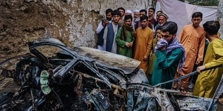KABUL, AFGHANISTAN -- AUGUST 30, 2021: Relatives and neighbors of the Ahmadi family gathered around the incinerated husk of a vehicle targeted and hit by an U.S. drone strike that was supposed to target ISIS-K suicide bombers but instead killed 10 civilians including 7 children, in Kabul, Afghanistan, Monday, Aug. 30, 2021. (MARCUS YAM / LOS ANGELES TIMES)